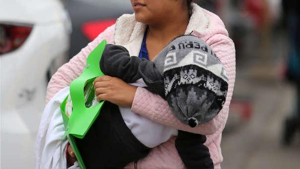 Una joven madre peruana sostiene a su hijo mientras ingresa al Instituto Materno Infantil, en la ciudad de Lima.