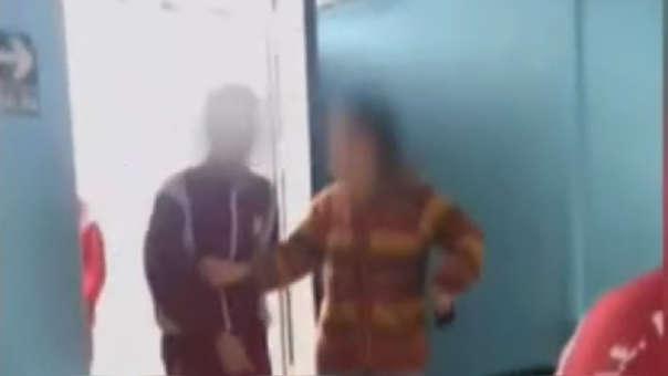 La maestra intenta que un par de alumnos no ingresen al salón; sin embargo, uno de ellos empuja la puerta con fuerza.