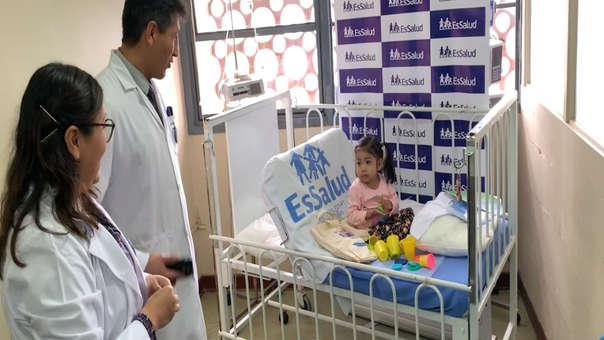 Niña de dos años acompañada por los médicos.