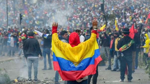Un manifestante envuelto en una bandera ecuatoriana durante los enfrentamientos con la policía.