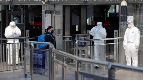 Miembros de seguridad protegidos con trajes asilantes esperan a la entrada del metro para tomar la temperatura a los pasajeros en Pekín.