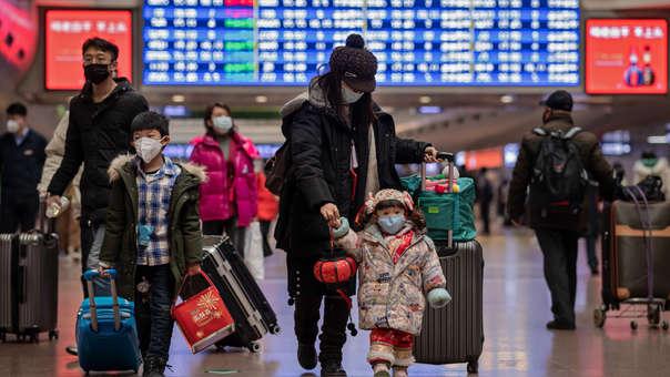 Una familia se moviliza por las festividades del Año Nuevo Lunar con mascarillas.