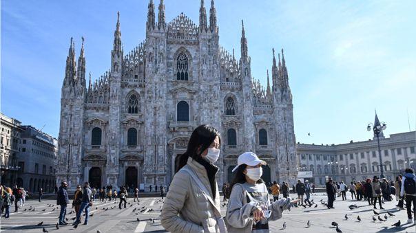 Dos mujeres usando mascarillas mientras cruzan la plaza del Duomo en el centro de Milán.