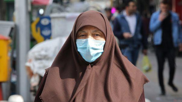 Una mujer usa una mascarilla para protegerse mientras camina por una calle de Teherán, capital de Irán.