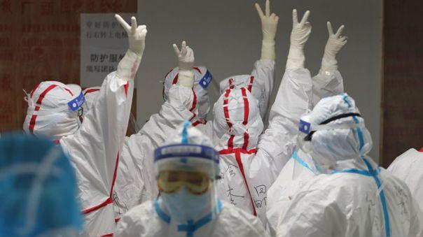Médicos chinos se dan ánimos antes de atender a pacientes con coronavirus en el hospital de la Cruz Roja en Wuhan, China, donde se originó la pandemia.