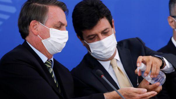 El presidente Jair Bolsonaro y el ministro de Salud Luiz Henrique Mandetta desinfectan sus manos y usan mascarillas antes de su conferencia de prensa.