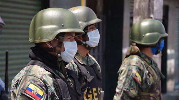 Militares usan mascarillas mientras resguardan la ciudad de Quito, que está bajo toque de queda.