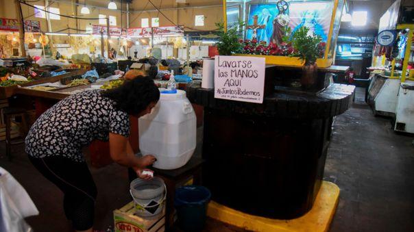 Una vendedora se lava las manos en un mercado local de la ciudad de Asunción frente al brote del nuevo coronavirus.
