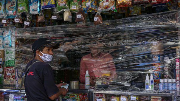 Un hombre vende productos cubierto con un plástico como medida preventiva ante el brote del nuevo coronavirus.