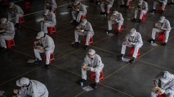 Trabajadores en un fábrica de Wuhan almuerzan respetando el aislamiento social.