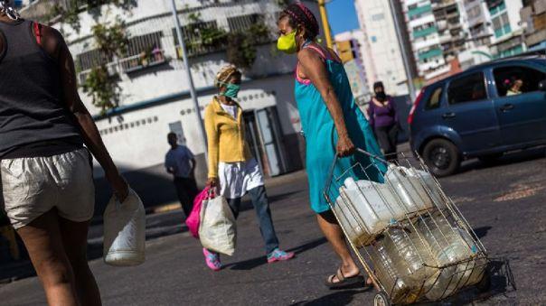 Una mujer con mascarilla con recipientes de agua en Caracas, Venezuela.
