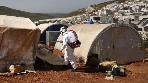 Un miembro de la Defensa Civil Siria, conocida como los 'Cascos Blancos', desinfecta una tienda de un campamento para desplazados por la guerra en este país.