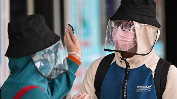 Una pareja en la estación de tren de Wuhan, la ciudad china donde se inició el coronavirus.