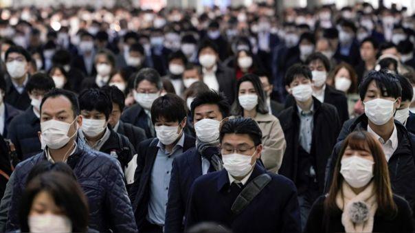 Trabajadores protegidos con mascarillas acuden a sus oficinas en Tokio, Japón, este lunes.
