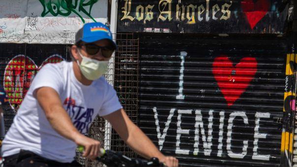 Un hombre con una máscara maneja su bicicelta en Venice Beache, una de las zonas más turísticas e icónicas de Los Ángeles, California.