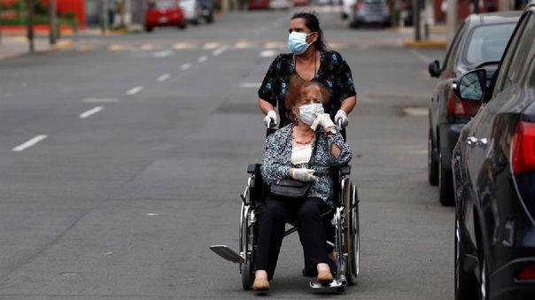 Una mujer es llevada en silla de ruedas en Lima. El Gobierno de Martín Vizcarra resolverá antes del Jueves Santo si alarga o no el confinamiento obligatorio.