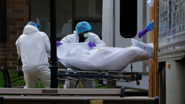 Trabajadores de salud sacan un cadáver de un camión frigorífico que sirve como morgue temporal en Brooklyn, Nueva York.