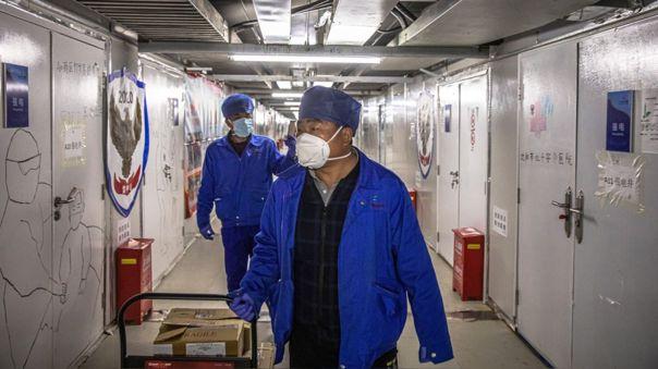 Trabajadores de salud con mascarillas en el hospital Leishenshan de Wuhan.  Las paredes tienen mensajes de ánimo escritos durante la crisis por el coroanvirus.