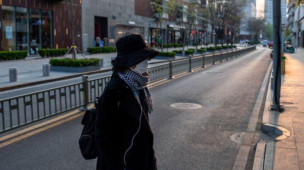 Una mujer con máscarilla camina por las calles de Pekín, capital de China.