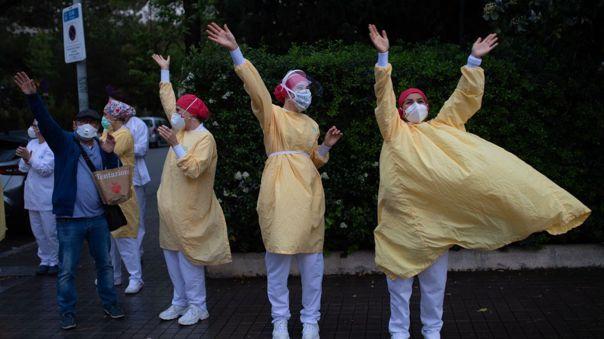 Trabajadoras de salud reciben los aplausos de ciudadanos españoles afuera del Hospital de Barcelona.