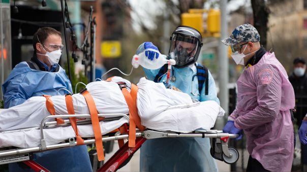 Bomberos y personal médico atienden a un anciano con dificultades para respirar durante el confinamiento en Nueva York.
