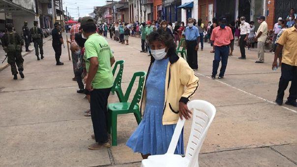 Autoridades colocan arias filas de sillas, a un metro de distancia, en los exteriores del Banco de la Nación para los ancianos que cobran pensión 65  en Iquitos, Loreto.