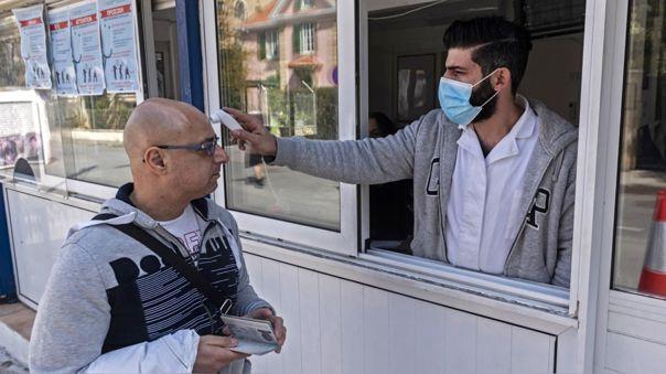 Un médico chipriota le toma la temperatura a un ciudadano al pasar por un punto de control.