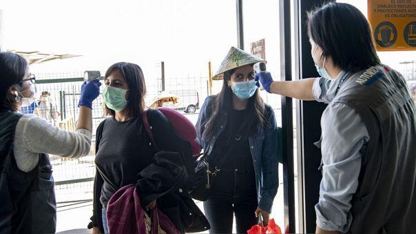 Autoridades toman la temperatura a pasajeros chilenos en el aeropuerto internacional de Santiago