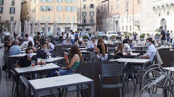 Italianos en un bar en una plaza de Brescia.