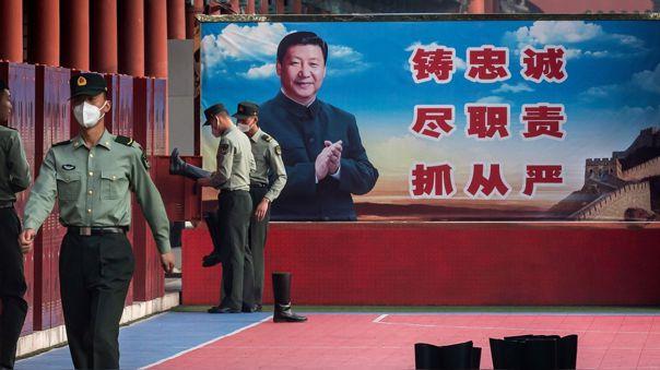 Soldados el Ejército de Liberacion chino junto a una representació del presidente de China, Xi Jinping.