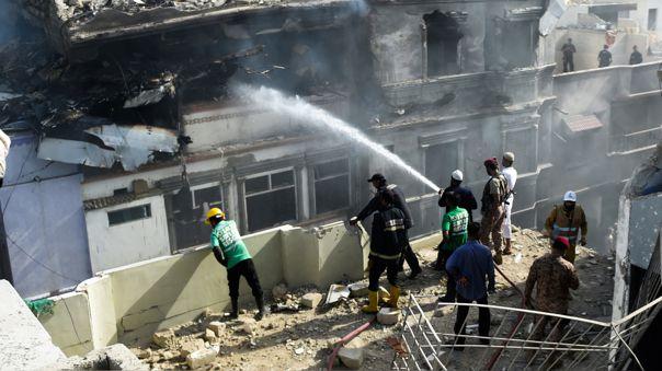 Un bombero rocía agua en un edificio quemado después de que un avión de Pakistan International Airlines se estrellara en una zona residencial de Karachi el 22 de mayo de 2020.