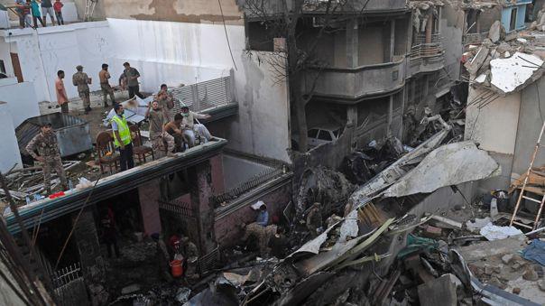 El personal de seguridad busca víctimas en los restos de un avión de Pakistan International Airlines después de que se estrelló en una zona residencial de Karachi el 22 de mayo de 2020.