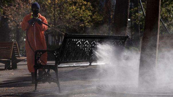 Un trabajador municipal desinfecta una banca en la Plaza de Armas de Santiago.