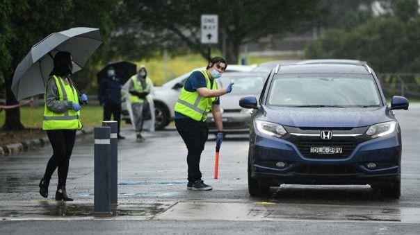 Trabajadores guian a conductores en Sydney, Australia.