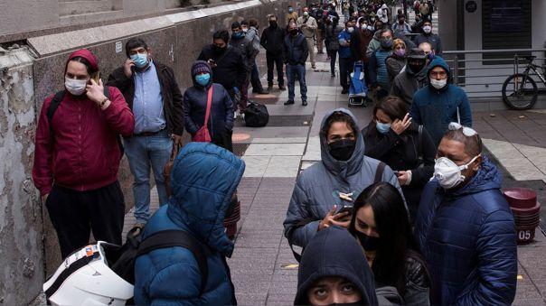Un grupo de personas hace cola para acceder a un banco en Santiago de Chile durante la cuarentena.