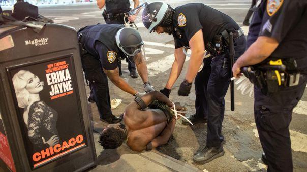 Policías de Nueva York detienen a un manifestante durante los desmanes registrados la noche del lunes en la ciudad.