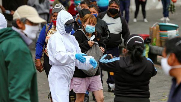 Ciudadanos ecuatorianos con tapabocas son vistos mientras caminan por las calles de Quito.