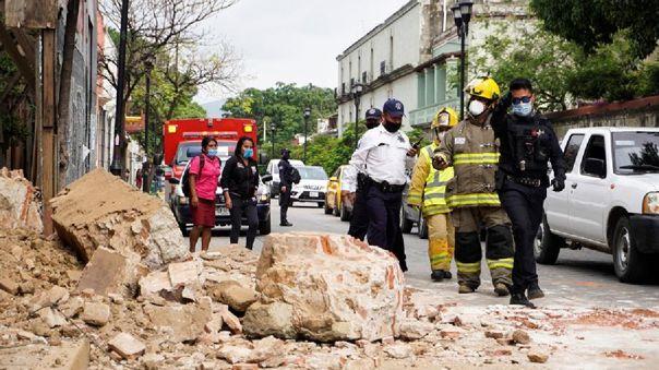 Miembros de la policía y de los bomberos observan los daños causados en una barda derrumbada este martes, en la ciudad de Oaxaca (México).
