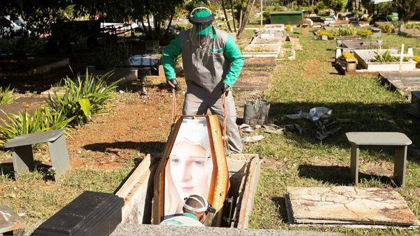 Trabajadores del cementerio Campo de Esperanza, en Brasilia, entierran a una víctima de coronavirus.