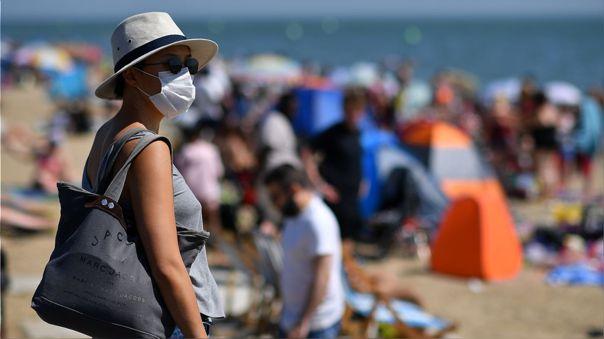 Una mujer con una mascarilla en una playa de Inglaterra.