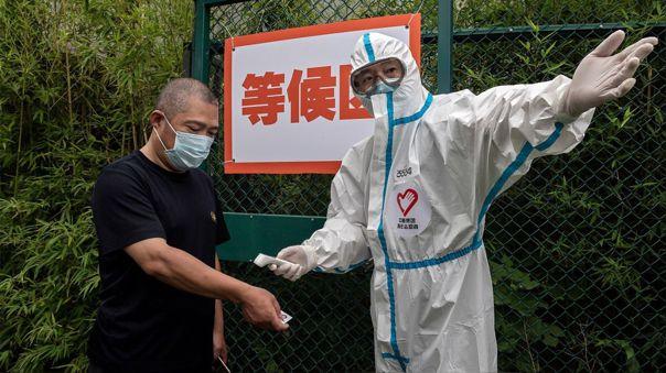 Un trabajador de salud le da indicaciones y toma la temperatura a un hombre que está por someterese a una prueba de descarte de COVID-19 en Pekín.