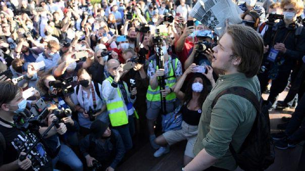 Periodistas rodean a un hombre que protesta contra las enmiendas a la Constitución.
