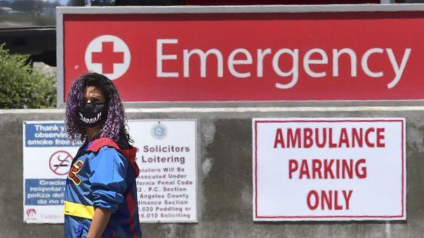 Una mujer joven con mascarilla afuera de un hospital en Los Ángeles, California, uno de los estados de EE.UU. donde los casos de coronavirus están en aumento.