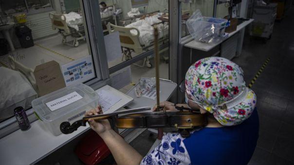La enfemera chilena Damaris Silva toca el violín para pacientes con COVID-19.