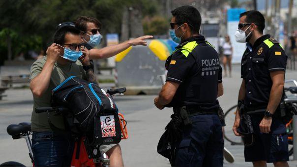 Policías le piden a ciudadanos usar sus mascarillas en la playa Barceloneta en Barcelona, Cataluña.