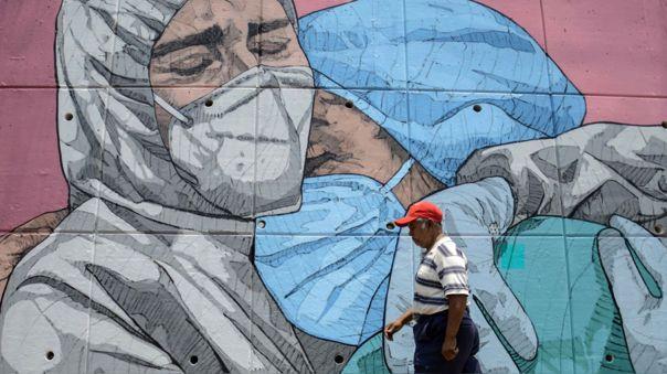 Coronavirus en México | Una mujer camina frente a un mural en Acaupulco dedicado a las victimas y a la lucha contra la COVID-19