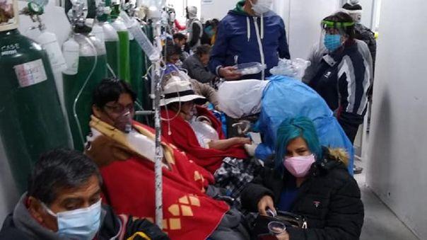 Pacientes COVID-19 en pasillos de hospital.