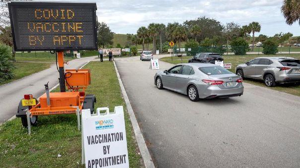 Personas hacen fila en sus vehículos para recibir la vacuna Pfizer-BioNTech contra la COVID-19