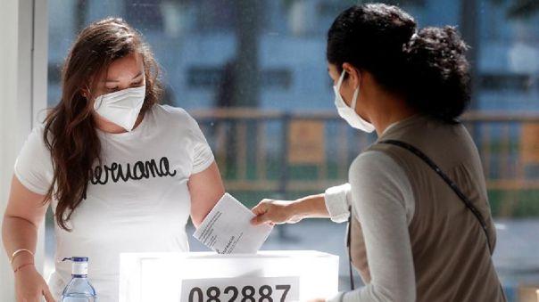 Una ciudadana peruana deposita el voto en el recinto del Palacio de Congresos en Valencia, España.