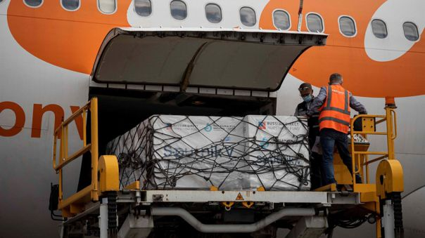 Personal aeroportuario descarga las cajas con vacunas Sputnik V